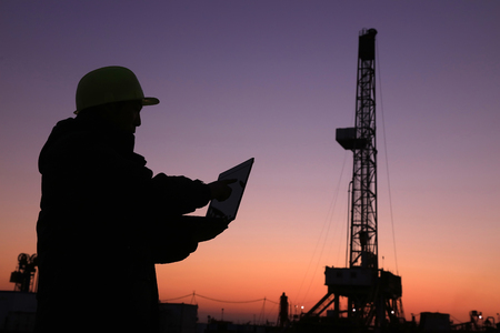 yacimiento petrolero: Marco de perforación de petróleo y técnico de la exploración en un campo petrolífero Editorial