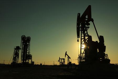 yacimiento petrolero: Haz de la unidad de bombeo equilibrada bajo el sol poniente en el campo petrol�fero Foto de archivo