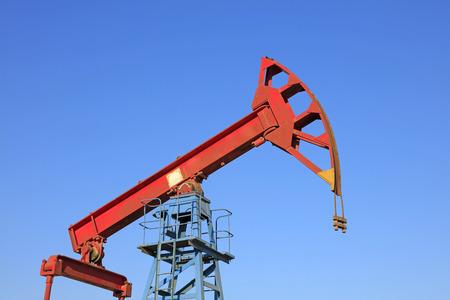 yacimiento petrolero: Unidad de bombeo de balancín bajo el cielo azul en el campo petrolífero