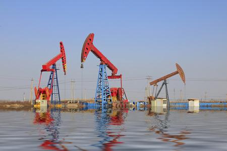 yacimiento petrolero: unidad de bombeo y la reflexi�n en el campo petrol�fero Foto de archivo