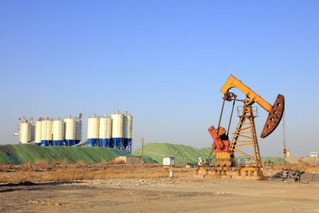 yacimiento petrolero: la unidad y la estación de mezcla de hormigón bituminoso de bombeo bajo el cielo azul en el campo petrolífero Foto de archivo