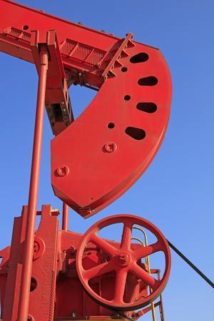 yacimiento petrolero: el bombeo de los componentes mecánicos de la unidad bajo el cielo azul en el campo petrolífero