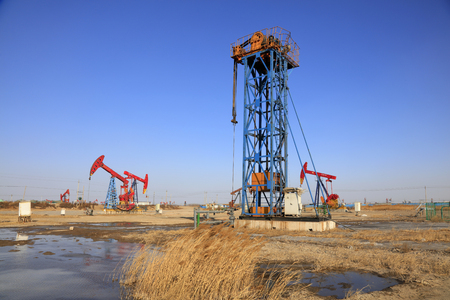 yacimiento petrolero: tower type pumping unit under blue sky in oilfield Editorial
