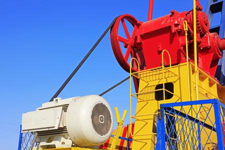 yacimiento petrolero: motor en la unidad de bombeo bajo el cielo azul en el campo petrolífero