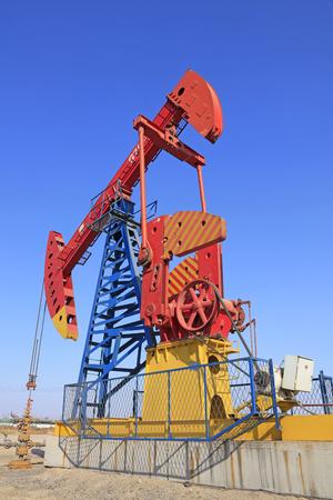 yacimiento petrolero: unidad de bombeo bajo el cielo azul en el campo petrolífero