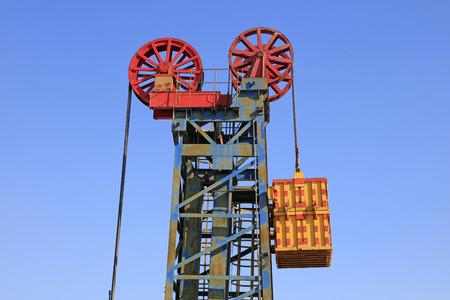 yacimiento petrolero: unidad de bombeo de tipo torre bajo el cielo azul en el campo petrolífero