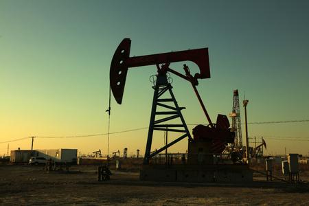 yacimiento petrolero: Haz de la unidad de bombeo equilibrada bajo el sol poniente en el campo petrol�fero Editorial
