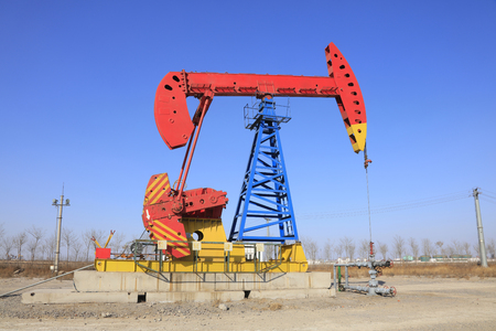 yacimiento petrolero: unidad de bombeo bajo el cielo azul en el campo petrol�fero