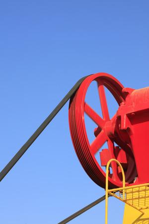yacimiento petrolero: ruedas de la maquinaria de petróleo bajo el cielo azul en el campo petrolífero Foto de archivo