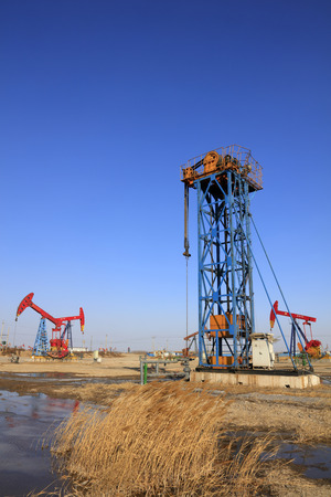 pumping unit: tower type pumping unit under blue sky in oilfield Editorial