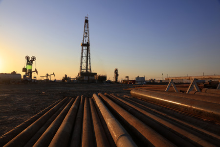 oilfield: Oil drilling derrick and pipelines in oilfield