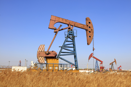 yacimiento petrolero: unidad de bombeo y la caña bajo el cielo azul en el campo petrolífero Editorial
