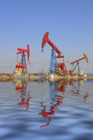 pumping unit: pumping unit and reflection in oilfield Stock Photo