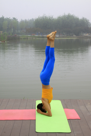 a woman doing yoga exercise in the park, luannan county, hebei province, China
