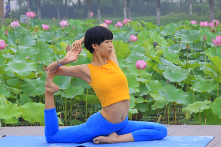 Luannan county - July 25: a woman doing yoga exercise in the park, on July 25, 2015, luannan county, hebei province, China