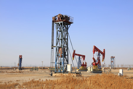 yacimiento petrolero: unidad de bombeo de tipo torre bajo el cielo azul en el campo petrol�fero