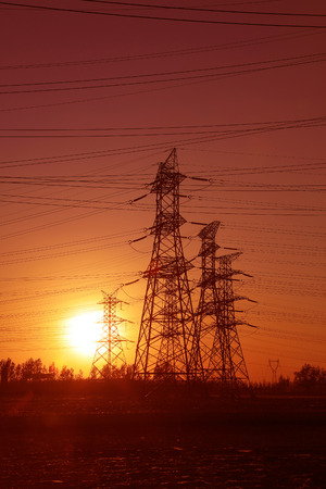 steel tower: high voltage electric power steel tower in the setting sun, closeup of photo