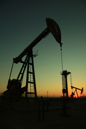 oilfield: Beam balanced pumping unit under the setting sun in oilfield
