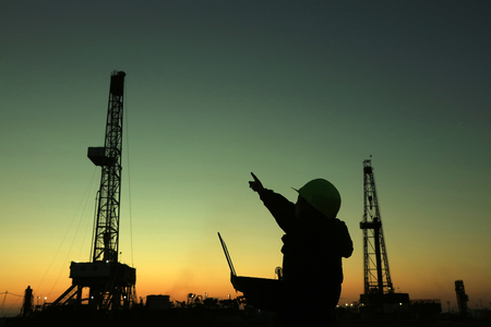 yacimiento petrolero: Marco de perforación de petróleo y técnico de la exploración en un campo petrolífero Foto de archivo