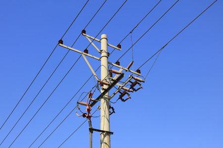 solid wire: telegraph poles under the blue sky, closeup of photo Stock Photo