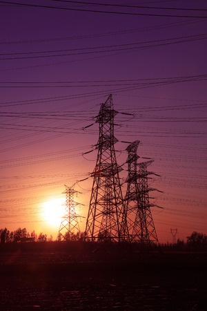 solid wire: high voltage electric power steel tower in the setting sun, closeup of photo