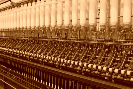 Textile spindles on the production line, closeup of photo Stock Photo