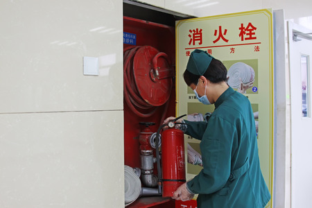 medical personnel: Luannan - June 29: medical personnel check the fire fighting equipment, in the hospital, on June 29, 2015, luannan county, hebei province, China