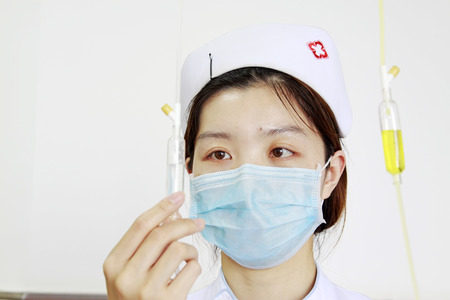 nurse hat: Luannan - June 29: nurse check infusion tube in the hospital, on June 29, 2015, luannan county, hebei province, China