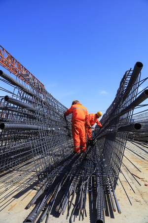 Workers welding steel components, closeup of photo