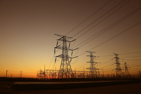 high voltage electric power steel tower in the setting sun Stock Photo
