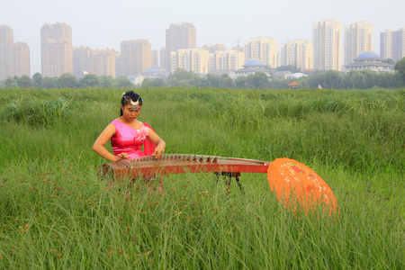 hebei: Luannan - August 8: girl playing guzheng in the park, August 8, 2015, luannan county, hebei province, China