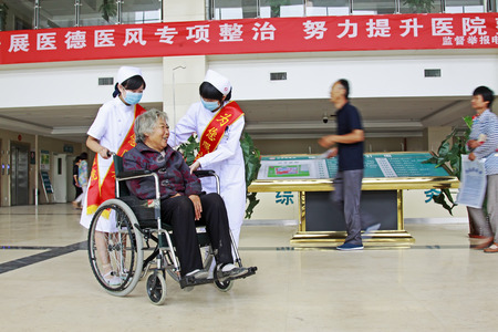 Luannan - June 29: nurse miss using a wheelchair push older patients in the hospital, on June 29, 2015, luannan county, hebei province, China