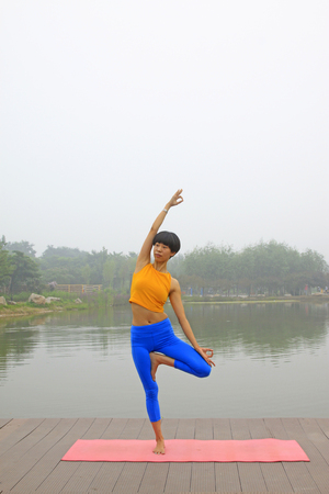 physique: Luannan county - July 25: A woman doing yoga exercise in the park, on July 25, 2015, luannan county, hebei province, China