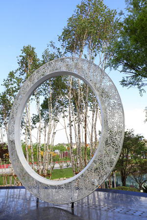 White ring sculpture in a park   Stock Photo