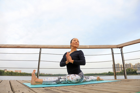 Luannan County - September 17, 2016: Woman practicing yoga in the park, Luannan County, Hebei Province, China.