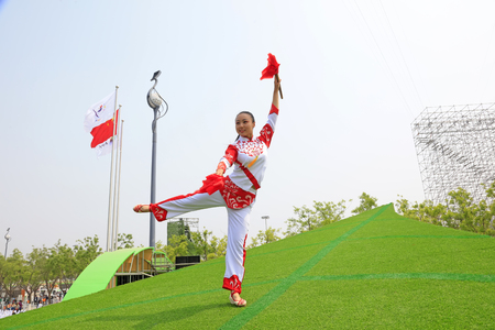 Tangshan City - April 29, 2016: a girl practices dance on the lawn, in the park, Tangshan City, Hebei, China Фото со стока - 122541865