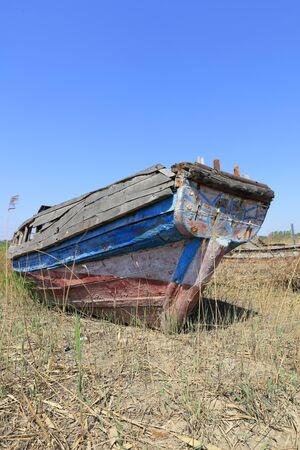 The broken wooden boat is on land