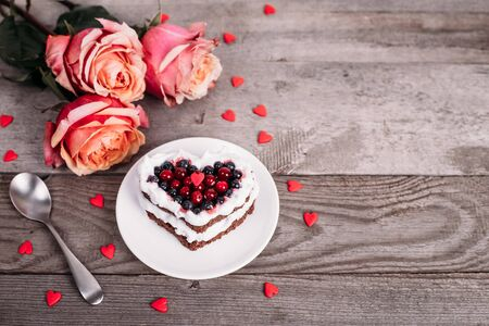 Mini romantic dessert cake for Valentine's Day with roses. Sweet cookies with cream topping and red heart for decor on wooden background. Close-up, copy space.