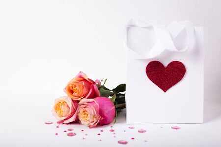 Roses and present gift in paper pack with red heart on white background/ Valentines day background Stock Photo
