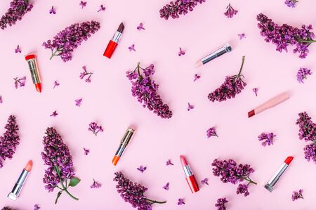 Beauty background with lipsticks and white lilac flowers on a pastel pink background. Modern make-up cosmetics. Top view. 스톡 콘텐츠