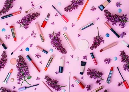 Beauty pattern background with face cosmetic products, lilac flowers on a pastel pink background. Modern spring make-up brushes and decorative cosmetics. Top view.