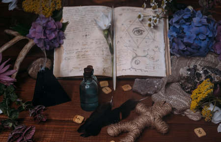 Open old book with magic spells, runes, black candle and herbs on witch table. Occult, esoteric, divination and wicca concept. Halloween vintage background