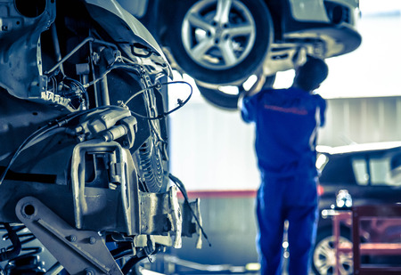 car manufacturing: Auto repair factory parked engine,Workers concentrate on work. Stock Photo