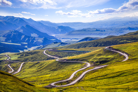 to bend: The rugged mountain road. Stock Photo