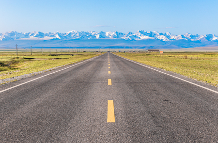 Een rechte weg onder de sneeuwberg. Stockfoto