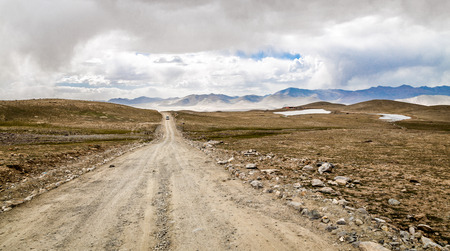 mountain landscape: The gravel road leading to the distance.