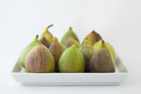 Purple green figs neatly arranged on square plate isolated on white