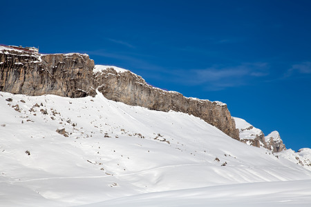 Rocky snow-covered mountain range with restaurant on top in Winter