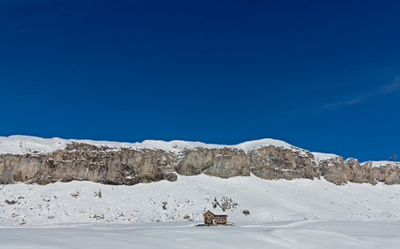 Snow surrounded house in front of a mountain range under blue skies