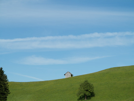 Small hut on grass slope in countryside with blue sky